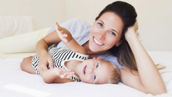 Мама лежит с ребенком на кровати счастливые
