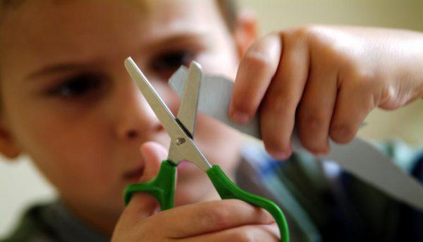 Мальчик вырезает из бумаги