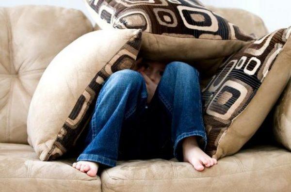 Ребенок прячется среди подушек