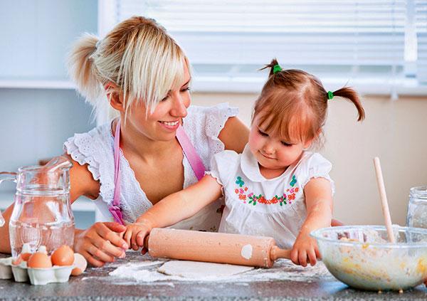 Дочка раскатывает тесто с мамой