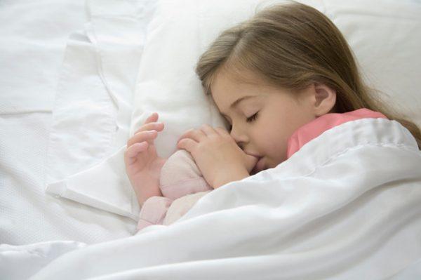 Девочка спит и сосет палец