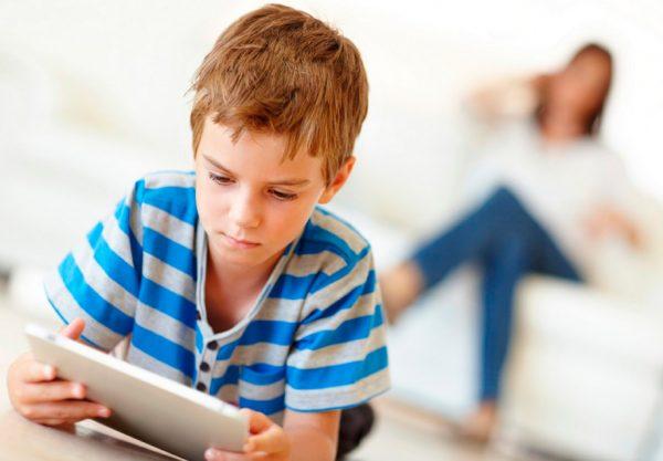 Мальчик играет на планшете