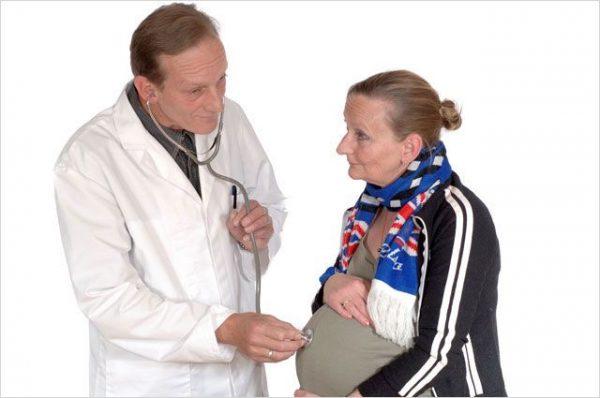 Доктор прослушивает живот беременной женщины
