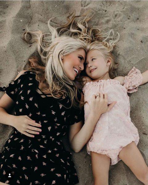Дочь с матерью улыбаются лежа на песке