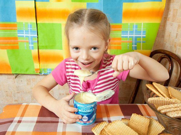 Девочка ест сгущенку