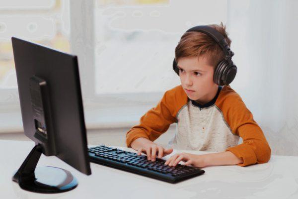 Мальчик в наушниках играет в компьютерную игру