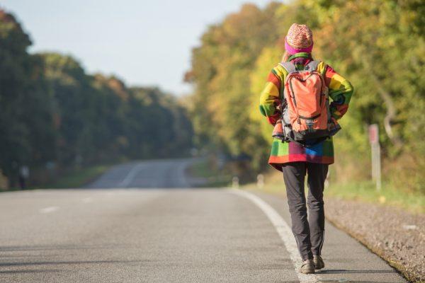 Девушка с рюкзаком идет по дороге