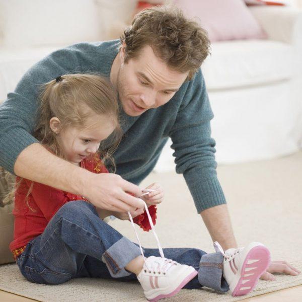Папа учит дочку завязывать шнурки