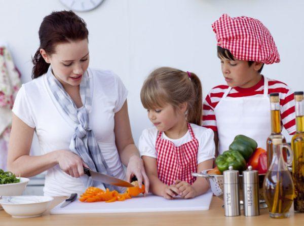 Мама показывает детям, как нарезать морковь