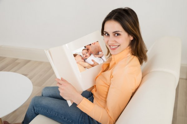 Женщина смотрит детский альбом
