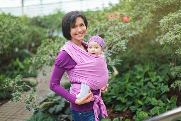 мама держит ребенка в слинге