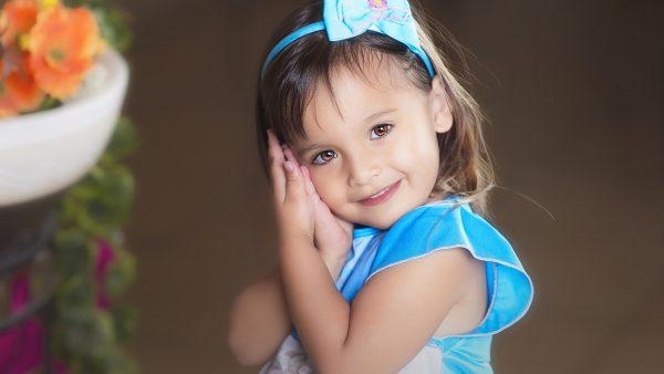 девочка с голубым бантиком и в голубом платьице улыбается