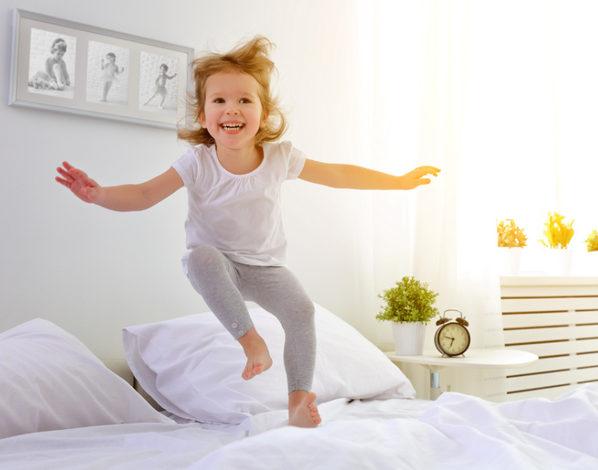 Девочка прыгает на кровати