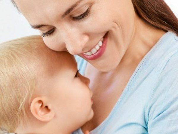 мама держит на руках малыша и улыбается
