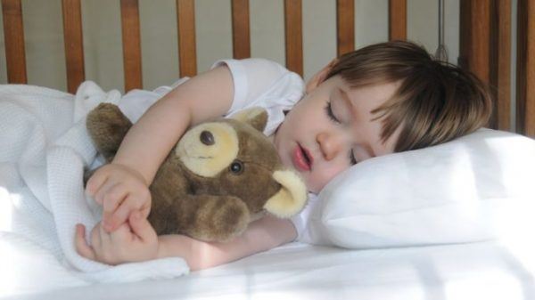 Малыш спит с медвежонком