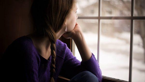 Девушка грустит и смотрит в окно