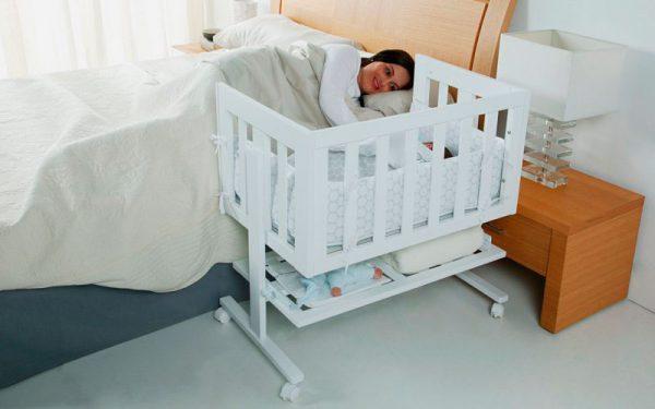 Малыш спит в приставной кроватке