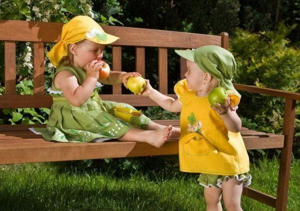 Девочка угощает подружку яблоком