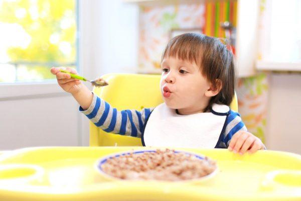 ребенок ест и играет