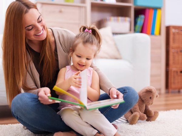 Мама рассматривает книгу с дочкой