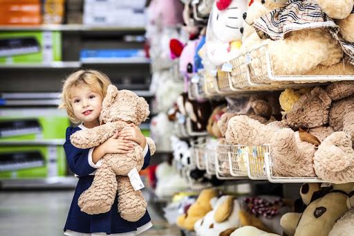 Девочка в магазине держит мишку