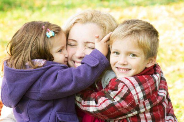 Мама обнимает двоих детей