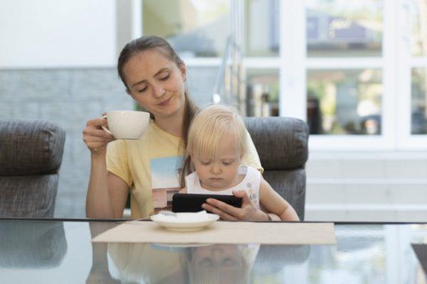 Мама с малышом на руках пьёт кофе