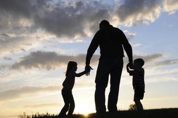 Отец гуляет с двумя детьми