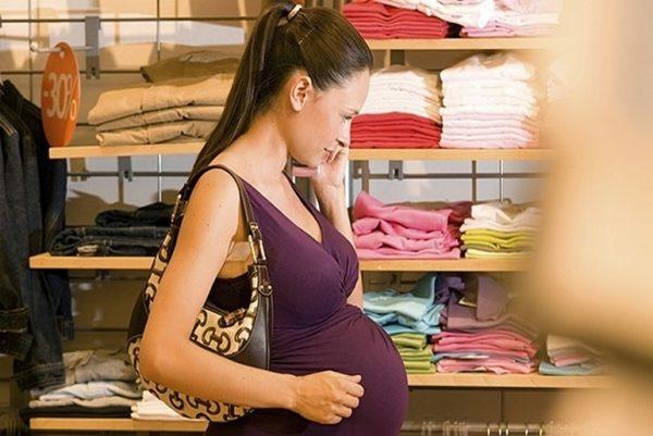 Беременная ходит по детскому магазину