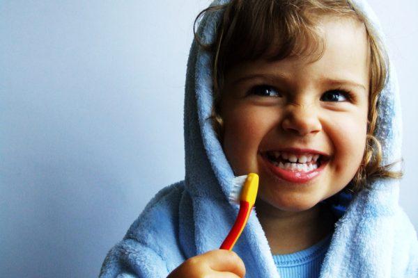 Девочка в голубом халате готовится чистить зубы желтой щеткой