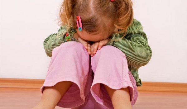 Девочка уткнулась в колени и плачет