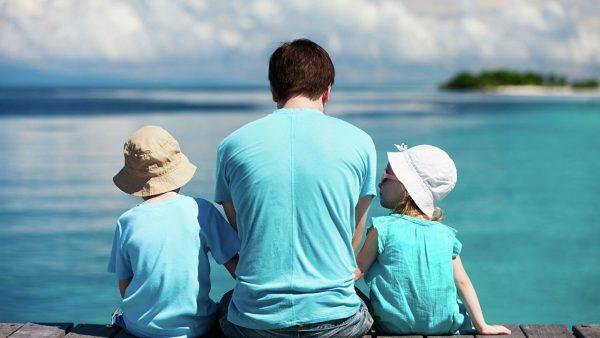 Отец с двумя детьми сидят у моря