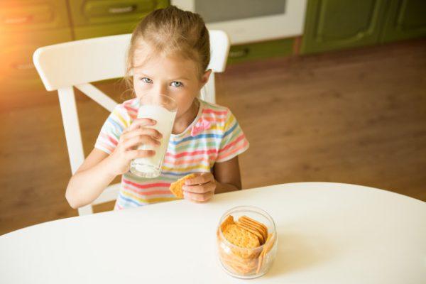 Девочка пьёт молоко с печеньем