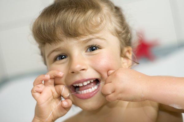 Девочка чистит зубы зубной нитью