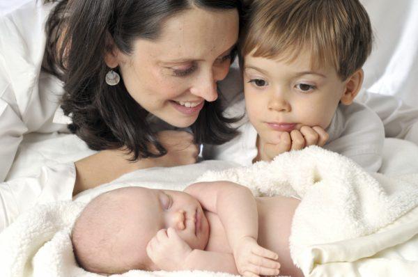 Мама с сыном смотрят на новорожденного