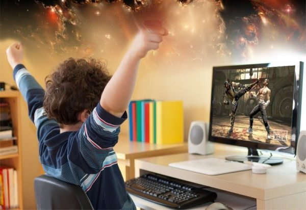 Мальчик играет в компьютерные игры и радуется