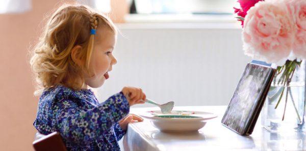 Девочка ест под мультик