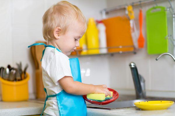 Маленький мальчик моет посуду