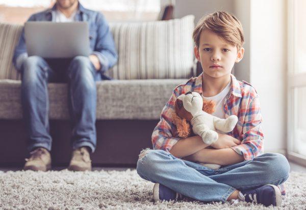 Мальчик с мягкой игрушкой грустит