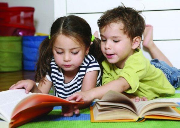 Девочка и мальчик рассматривают книгу
