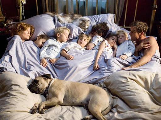 Родители лежат в кровати с детьми и животными