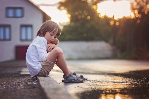 Одинокий мальчик сидит на улице
