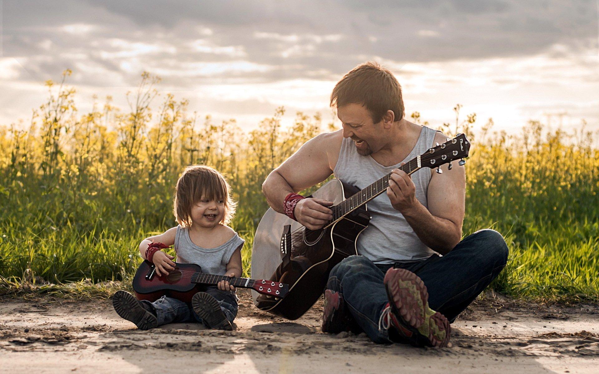 папа и сын играют на гитаре
