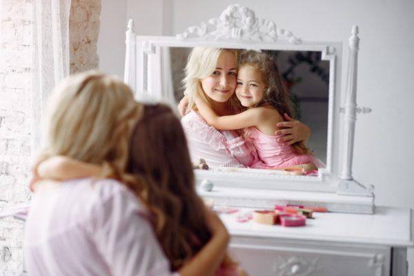 Женщина с дочкой смотрятся в зеркало