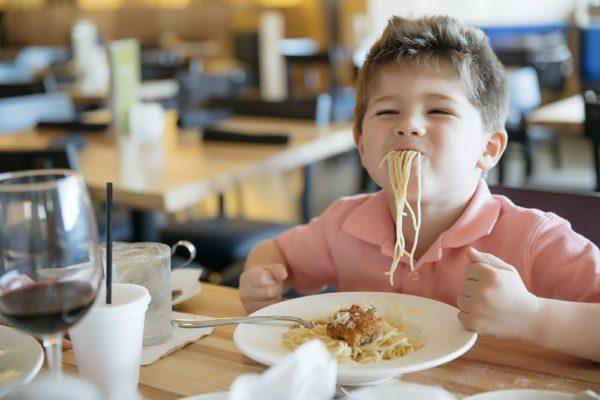 Мальчик сидит в кафе и ест спагетти