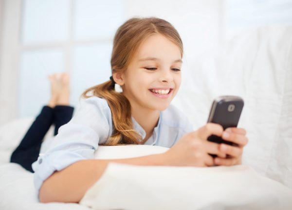 Девочка смотрит в свой телефон