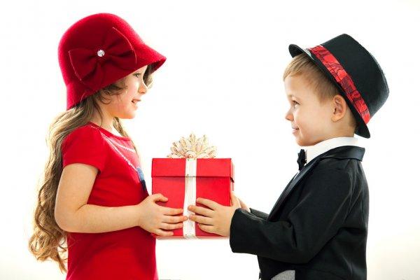 Мальчик дарит девочке подарок