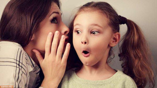 Мама что-то рассказывает дочке на ухо
