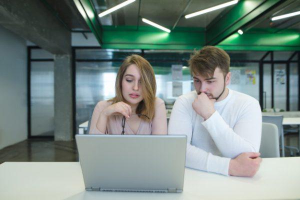 Пара сидит перед ноутбуком