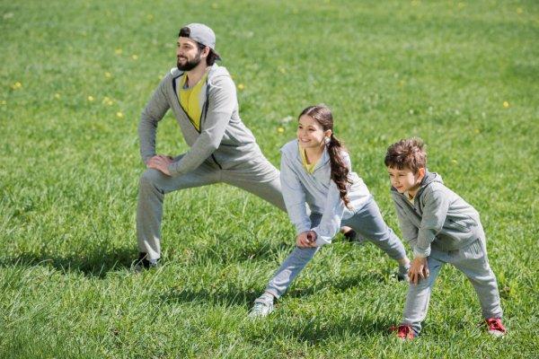 Девочка и мальчик занимаются с отцом физкультурой